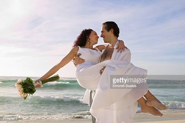 Groom carrying bride on beach