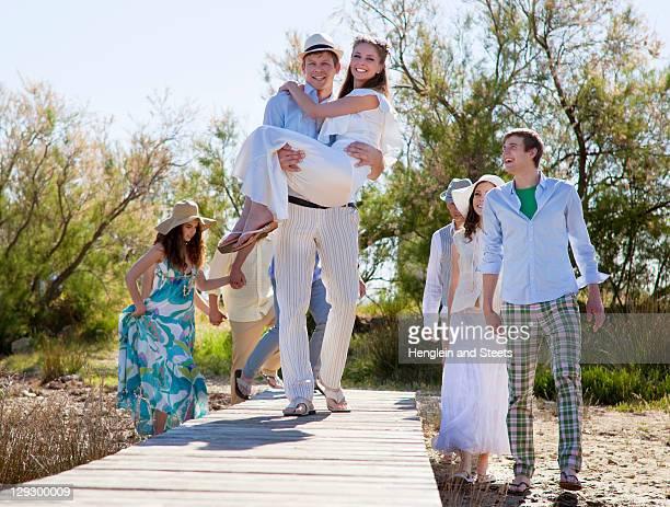 Groom carrying bride on deck