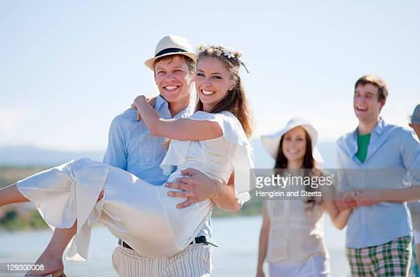 Groom carrying bride outdoors