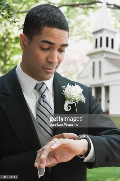 Groom checking wristwatch