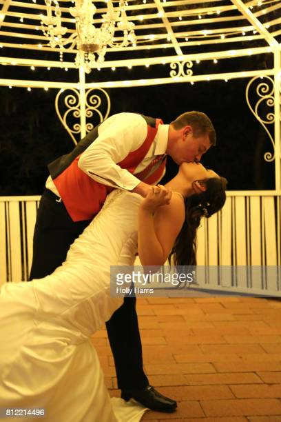 Groom dipping bride and kissing in gazebo at night