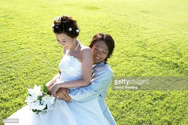 Groom embracing bride in the field