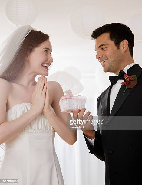 Groom giving Bride a present on their wedding day