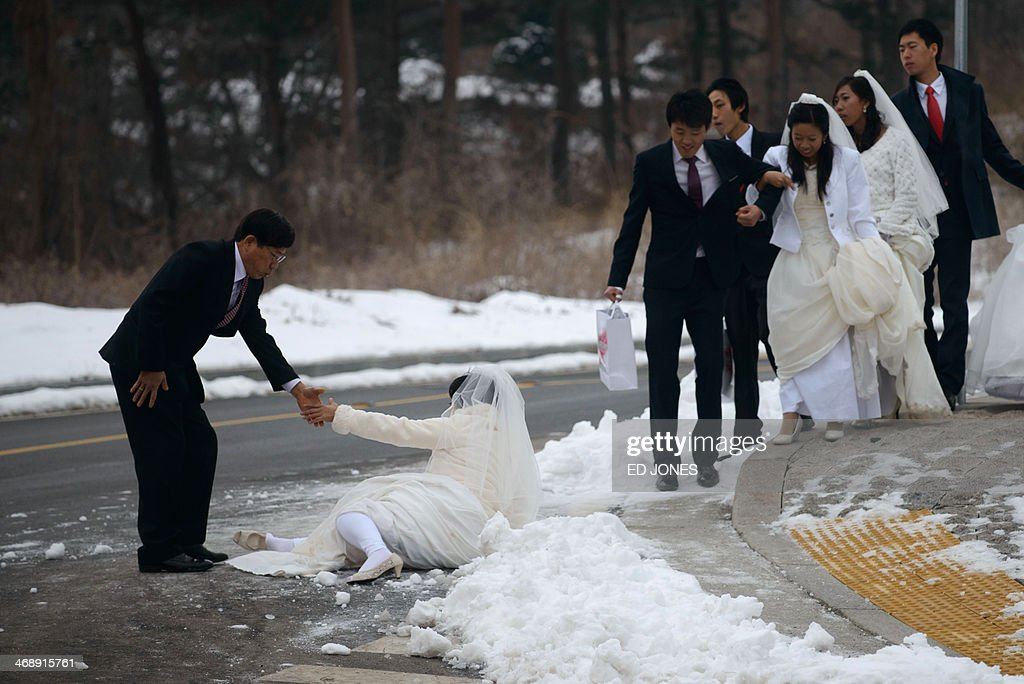 A groom helps his bride after she slipped on the ice as they arrive for a mass wedding event held by the Unification Church in Gapyeong on February 12, 2014. Unification Church members forming 2500 couples from 52 countries were married in a mass wedding in South Korea -- only the second such event since the death of their 'messiah' and controversial church founder Sun Myung Moon. AFP PHOTO / Ed Jones