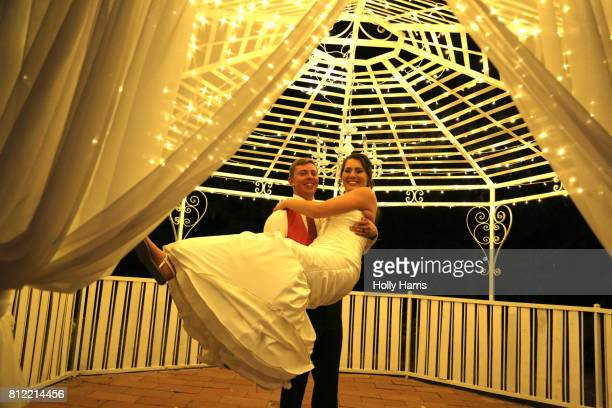 Groom holding up bride in his arms in gazebo