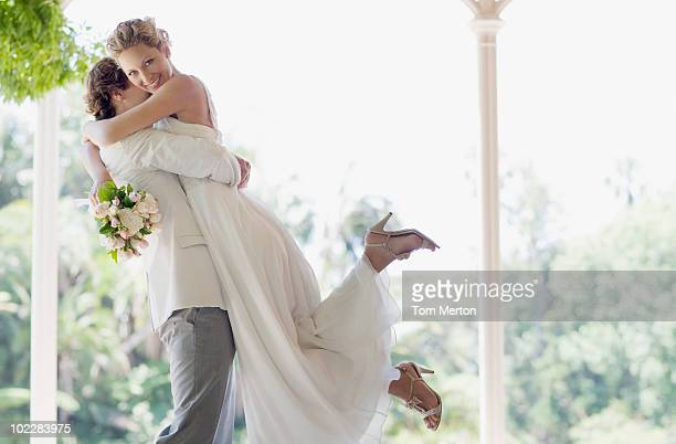 Groom hugging and lifting bride