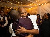 Groom hugging groomsman at reception