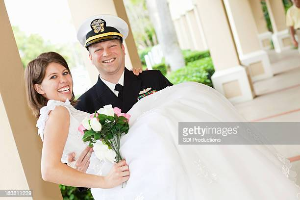 Groom in Navy Uniform Holding His New Bride