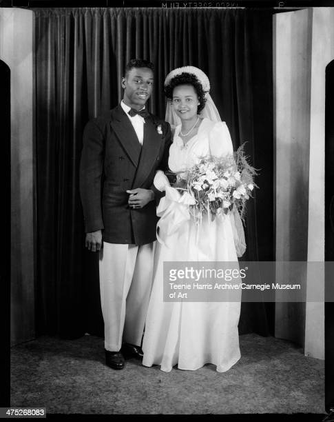 Groom Joseph H Mixon Jr wearing dark jacket with rounded lapels and light colored pants and bride Emma Glass Mixon wearing gown with sweetheart...