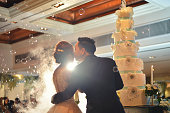 Groom kisses bride in front of cake in wedding ceremony in hall