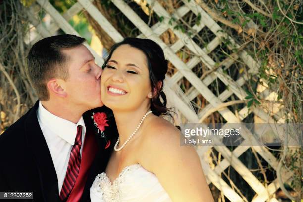 Groom kissing smiling bride on the cheek