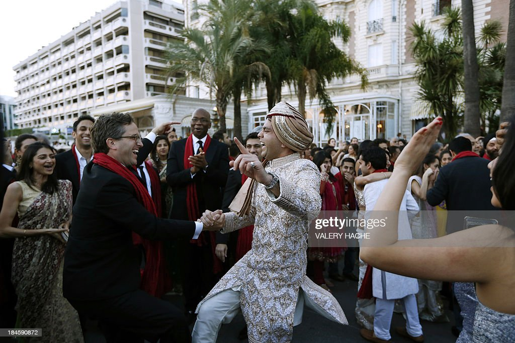 Groom Kunal Grover (C) dances in front of the Carlton Hotel in the southeastern French city of Cannes on October 14, 2013 during his wedding party. The Carlton palace was entirely booked for several nights to accomodate guests for the wedding of Grover and Ria Dubash.