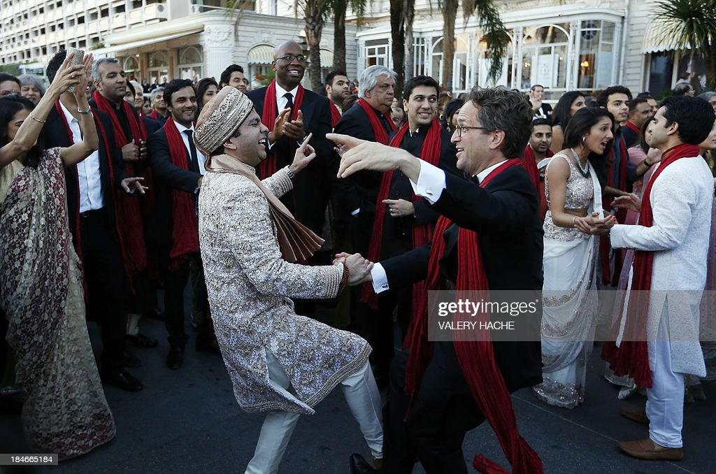 Groom Kunal Grover (L) dances in front of the Carlton Hotel in the southeastern French city of Cannes on October 14, 2013 during his wedding party. The Carlton palace was entirely booked for several nights to accomodate guests for the wedding of Grover and Ria Dubash.