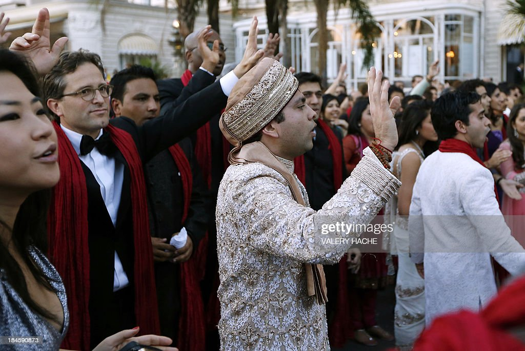 Groom Kunal Grover (C) gestures in front of the Carlton Hotel in the southeastern French city of Cannes on October 14, 2013 during his wedding party. The Carlton palace was entirely booked for several nights to accomodate guests for the wedding of Grover and Ria Dubash.