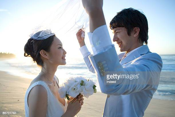 Groom lifting bride's veil on beach, smiling