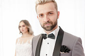 Gorgeous businessman or groom man portrait in suit elegant clothes, blurred woman on white background. Proud man, wedding day