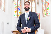 Groom on wedding waiting for bride at altar