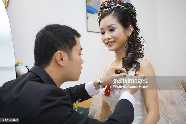 Groom pinning corsage on bride's dress
