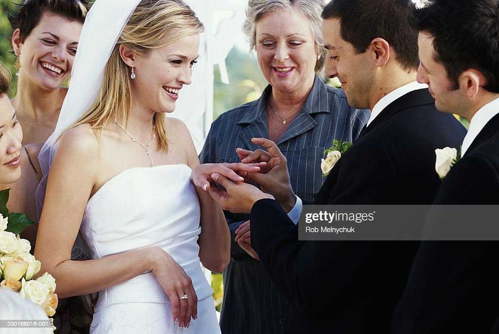 Groom Placing Ring On Brides Finger During Wedding Ceremony Stock Photo