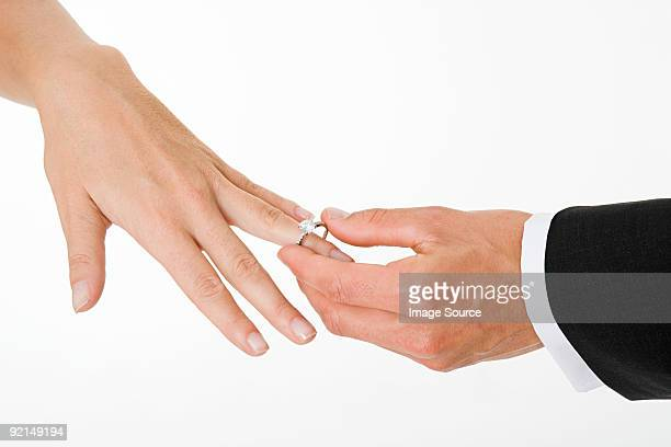 Groom placing ring on brides finger