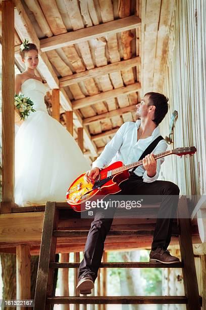 Bräutigam spielt Gitarre für die Braut. Das Brautpaar