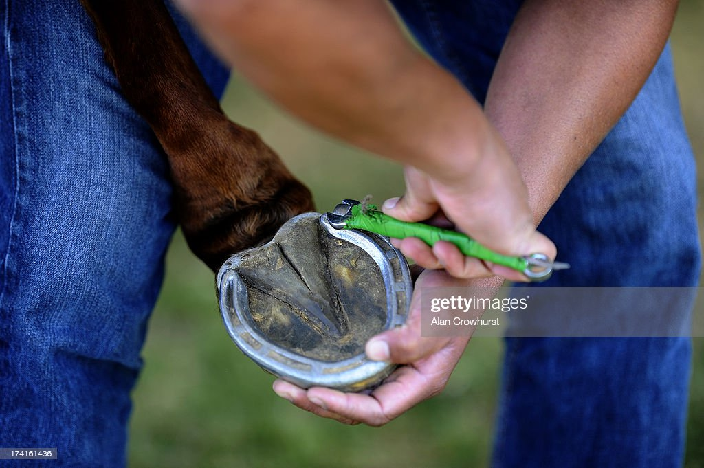A groom prepares a pony's hoof during the The Veuve Clicquot Gold Cup for the British Open Polo Championship Final between Dubai and Zacara at Cowdray Park Polo Club on July 21, 2013 in Midhurst, England.