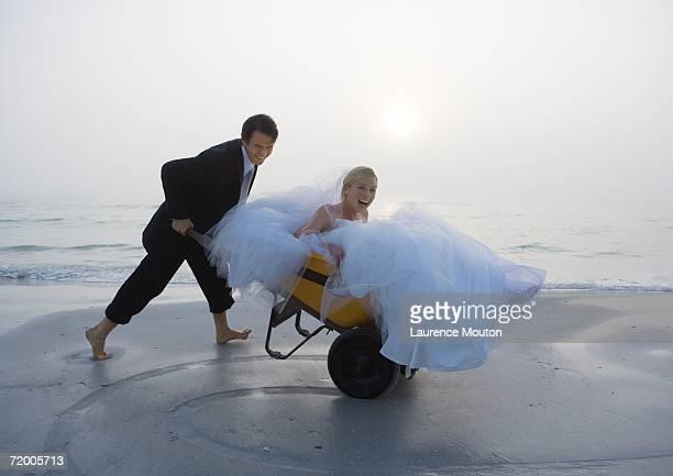 Groom pushing bride in wheelbarrow on beach