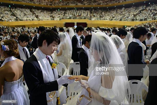 A groom puts a ring on the finger of his bride as they are married during a mass wedding event held by the Unification Church in Gapyeong on February...