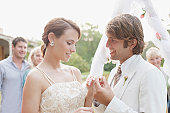 Groom putting ring on brides finger