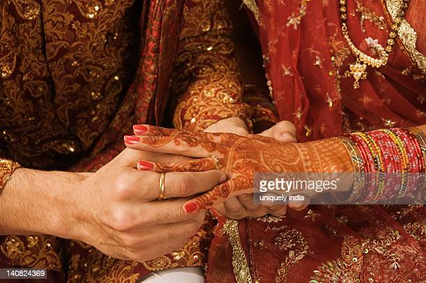 Groom putting wedding ring on a bride's finger