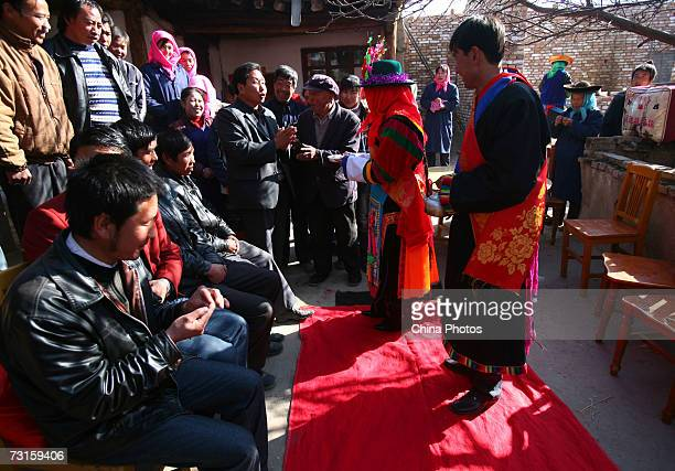 Groom Qi Xinghe and bride Luo Jinhua present wine to relatives during a Tu ethnic minority group wedding ceremony on January 30 2007 in Huzhu County...