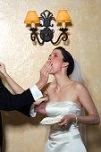 Groom shoving wedding cake into bride's mouth