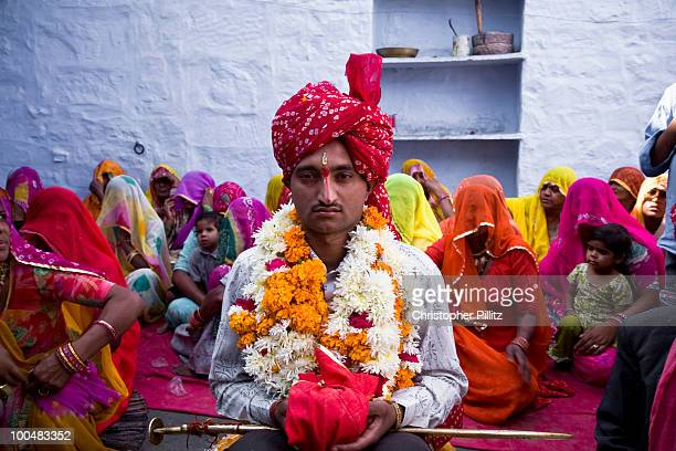 Groom sits patiently at his wedding ceremony