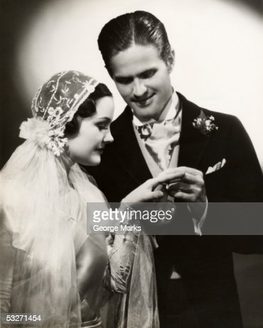 Groom slips wedding ring on bride's finger : Stock Photo