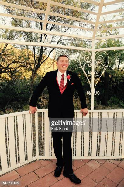 Groom smiling, standing in a gazebo