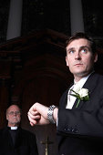Groom standing in church checking wristwatch, watched by vicar