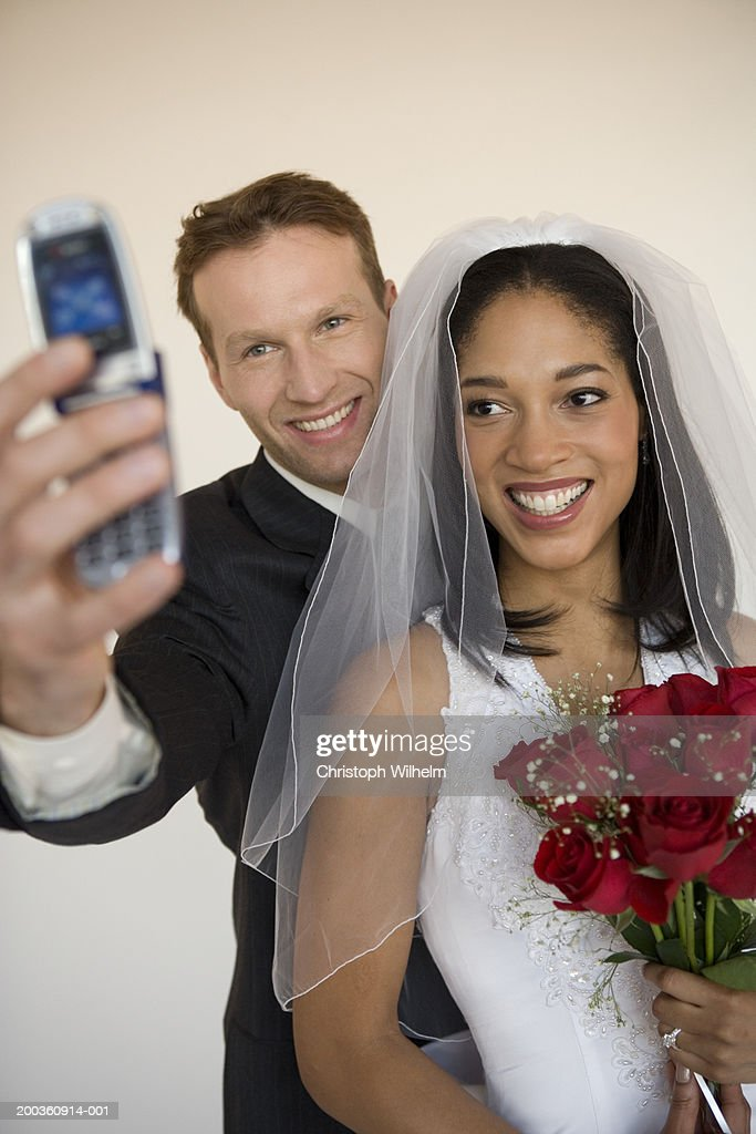 Groom taking photo of bride and himself, using camera phone : Stock Photo