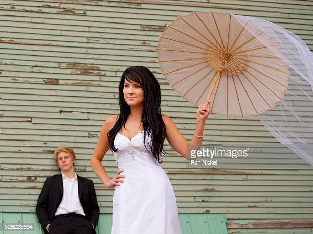 Groom watching a bride holding a parasol