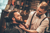 Side view of young bearded man getting beard haircut at hairdresser while sitting in chair at barbershop