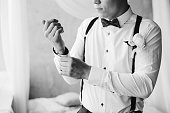Grooms morning preparation handsome groom in bow tie suspenders getting dressed and preparing for the wedding at hotel the bridegroom wears cufflinks in a white shirt black and white portrait closeup.