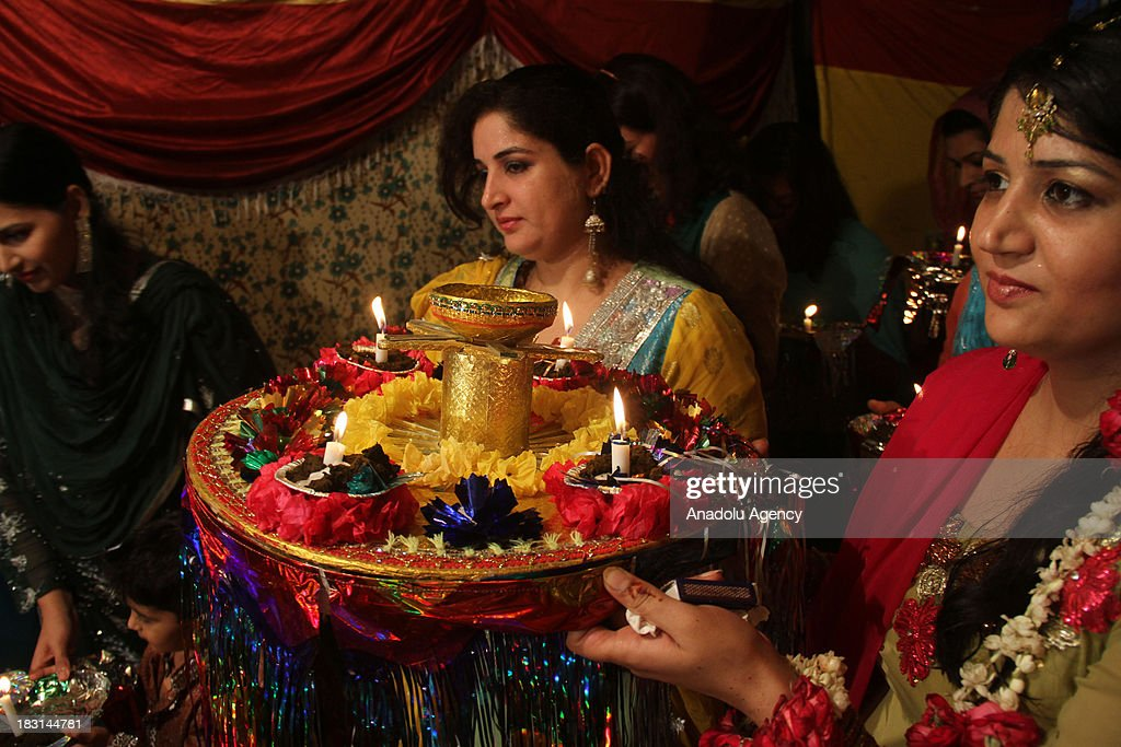 Groom's sisters bring traditional plate filled with henna and candles to stage during a henna ceremony on October 4, 2013 in Rawalpindi, Pakistan. Traditional meal such as halwa poori, aloo bhujia, rice and haleem is being served at the ceremony. As the weather is getting colder, people show high demand for the marriage in Pakistan. The Young segment of Pakistan's population is growing rapidly and its covers around 35 percent of the population.