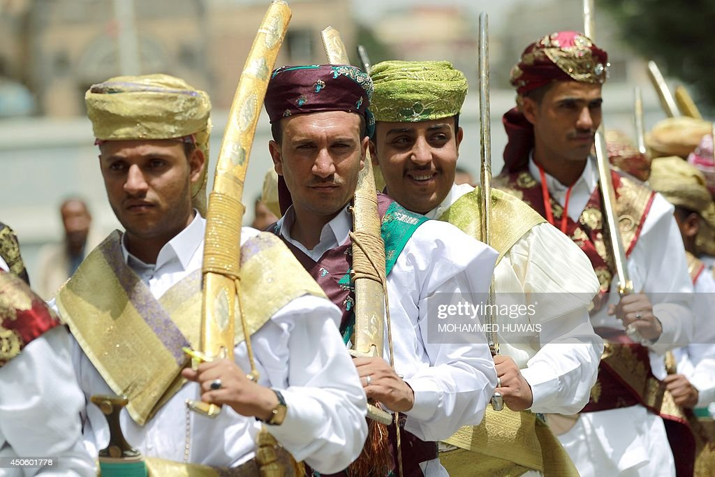 Grooms, who are employees of the Sanaa Municipality, wear traditional costumes and carry swords during a mass wedding ceremony on June 14, 2014, in the capital Sanaa. The ceremony was organized by the municipality for 350 members of its staff. AFP PHOTO / MOHAMMED HUWAIS