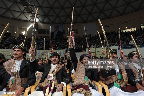 Grooms who are members of the Orphan Foundation for Development wear traditional costumes as they hold up their swords during a mass wedding ceremony...