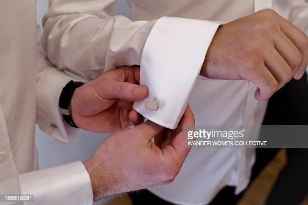 Groomsman helping groom with cufflink