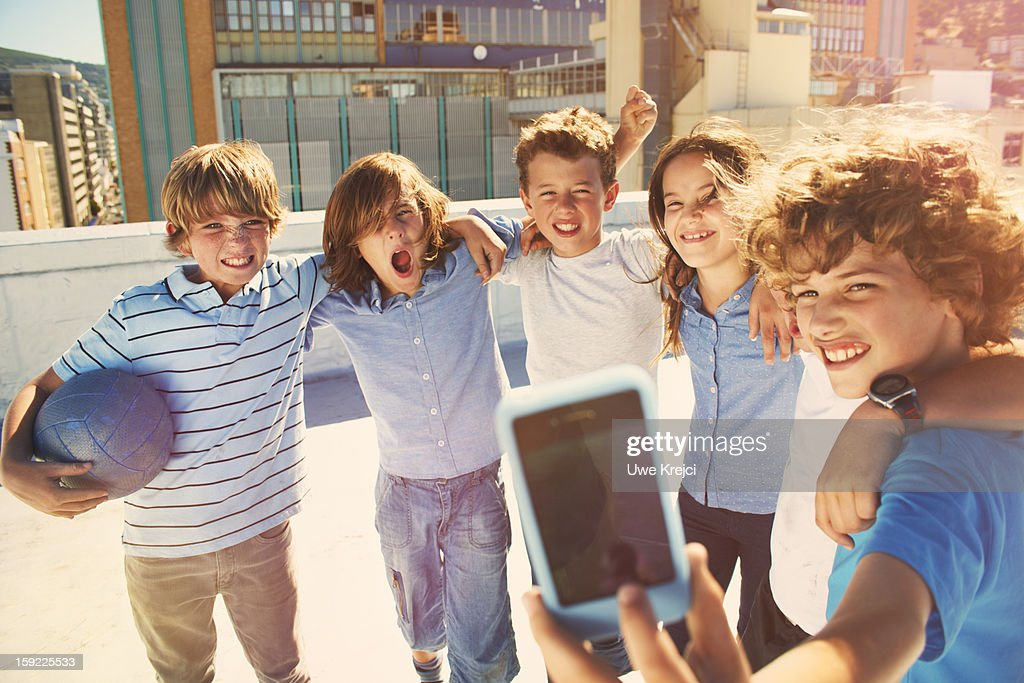 GrouChildren taking self-portrait with smart phone : Stock Photo