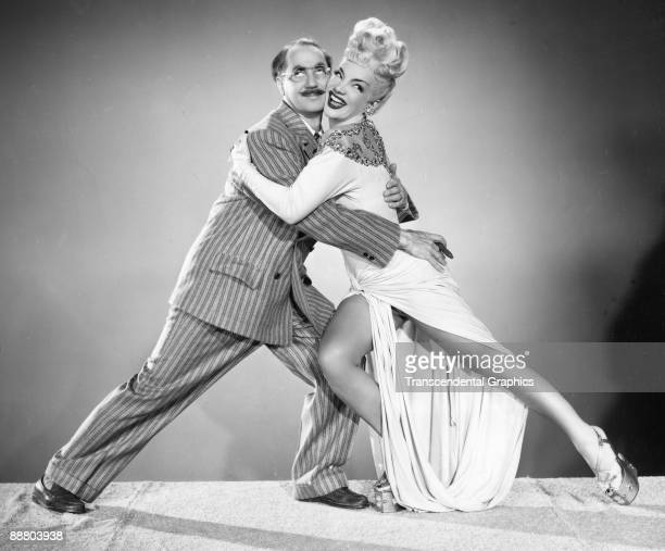 Groucho Marx and Carmen Miranda do a dance number for photographers during a publicity photo session in New York around 1950