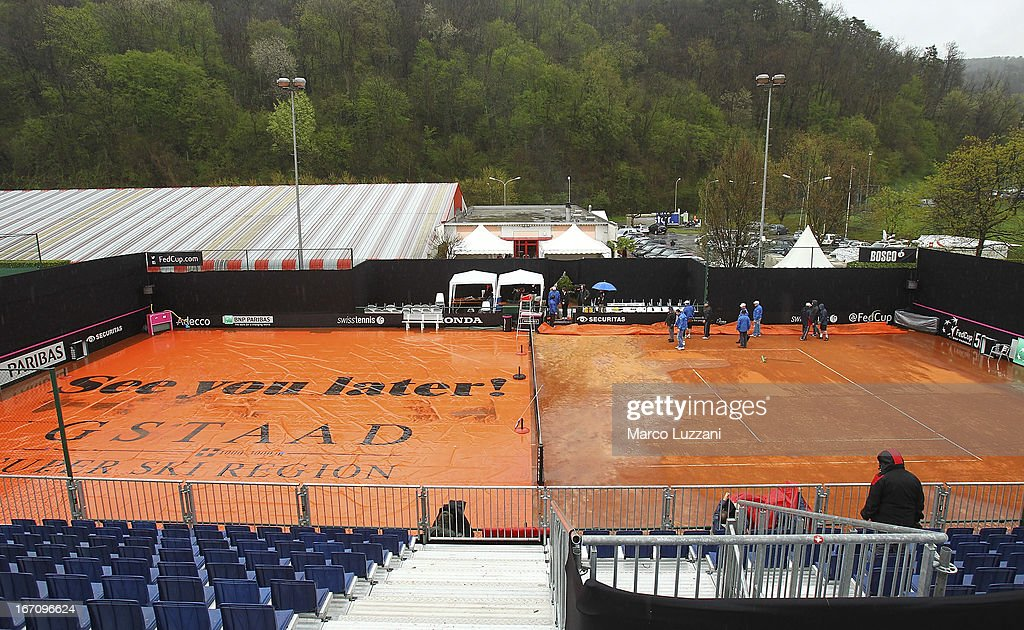 Groud staff work on the central court after a rain storm during day one of the Fed Cup World Group Play-Offs between Switzerland and Australia at Tennis Club Chiasso on April 20, 2013 in Chiasso, Switzerland.