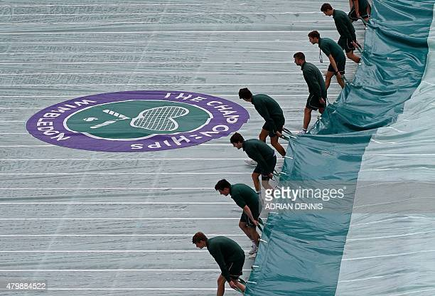 Groudstaff remove the court covers after a rain shower temporarily halted play in the men's quarterfinals match between Switzerland's Roger Federer...
