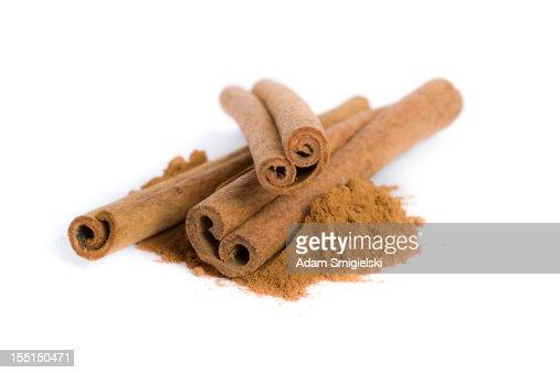 ground cinnamon and cinnamon sticks isolated on white