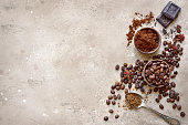 Ground coffee and coffee beans with spices over beige rustic slate, stone or concrete background.Top view with copy space.